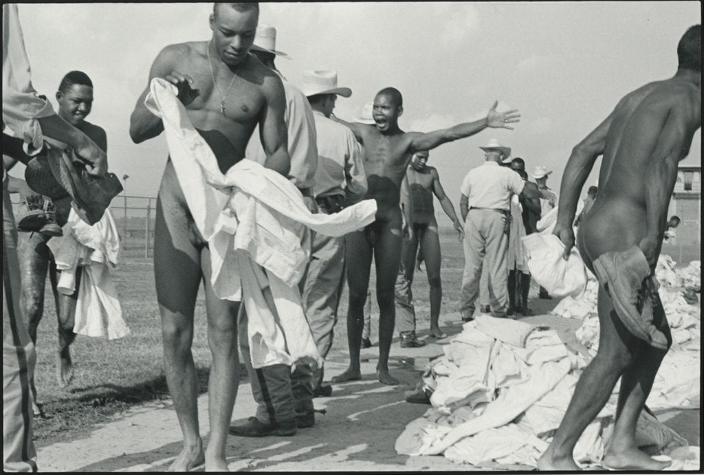 Black-and-white photograph of nude Black men being searched by white prison guards