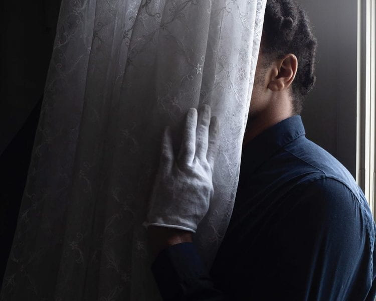 Photograph of a Black person standing beside a white lace curtain, their face hidden by the cloth, one white-gloved hand on the curtain.