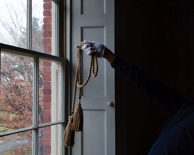 figure, leaning backwards so as to have their torso cloaked in shadow, standing by a window, holding a thick tasseled cord with a white-gloved hand