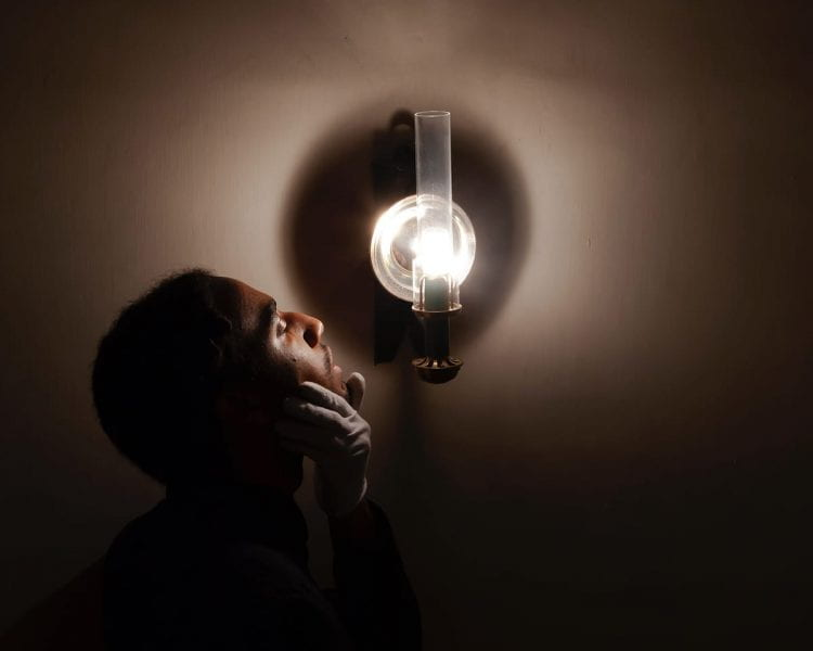 Photograph of a Black man, his head turned upward from the shadows toward a lighted wall sconce, his white-gloved hand on his chin