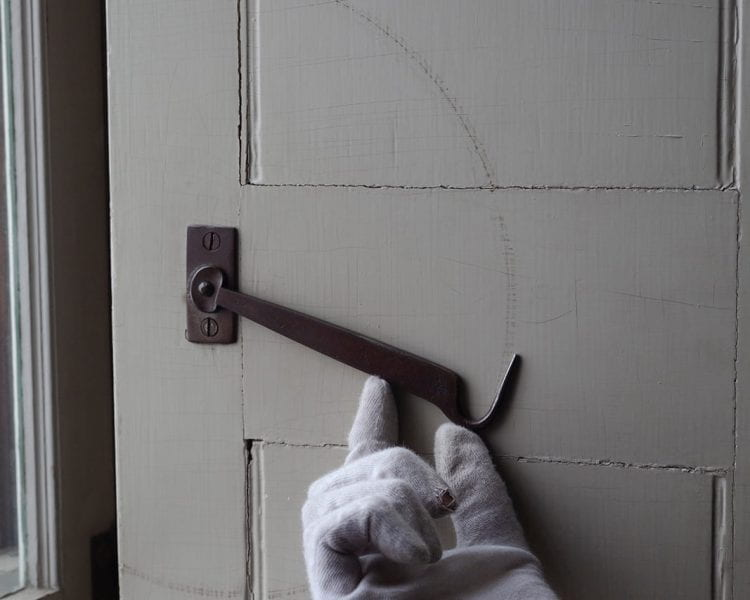 Photograph of a white gloved hand lifting a hook lock on a white door