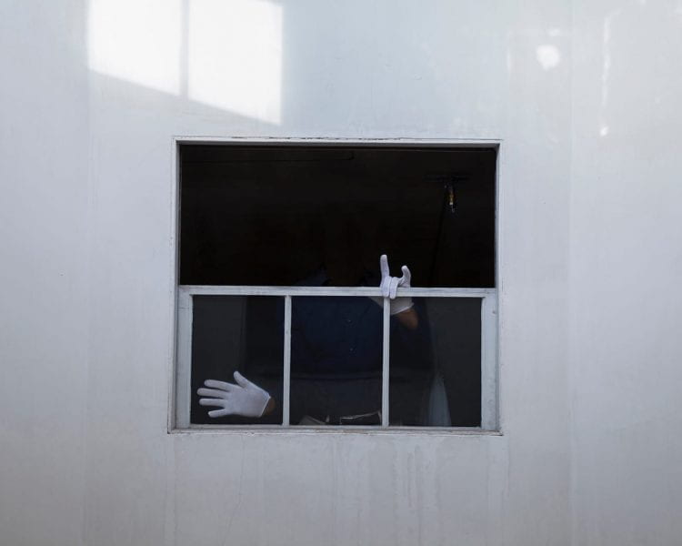 View of a window from outside. We see only the white-gloved hands of someone inside.