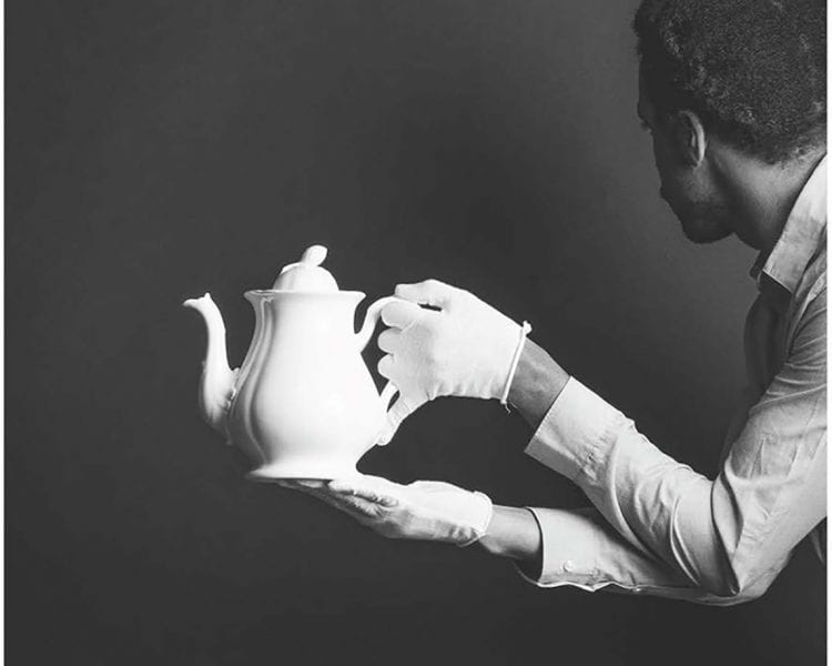 Photograph of a Black man's arms and head from the side, wearing a pale, collared shirt and bright white gloves, holding a similarly bright white teapot in front of a smooth, dark background.