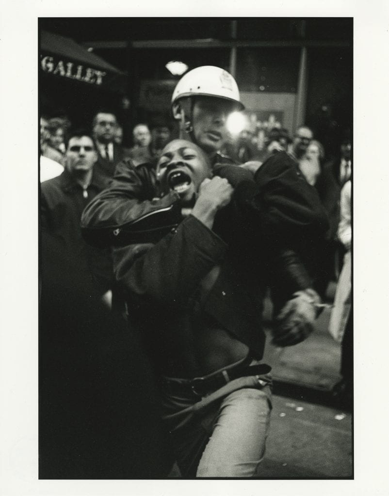 Black and White photograph centered on White, helmeted police officer as he drags a Black teenager by the neck in a chokehold, amidst a grown of mostly White onlookers in a crowded street scene