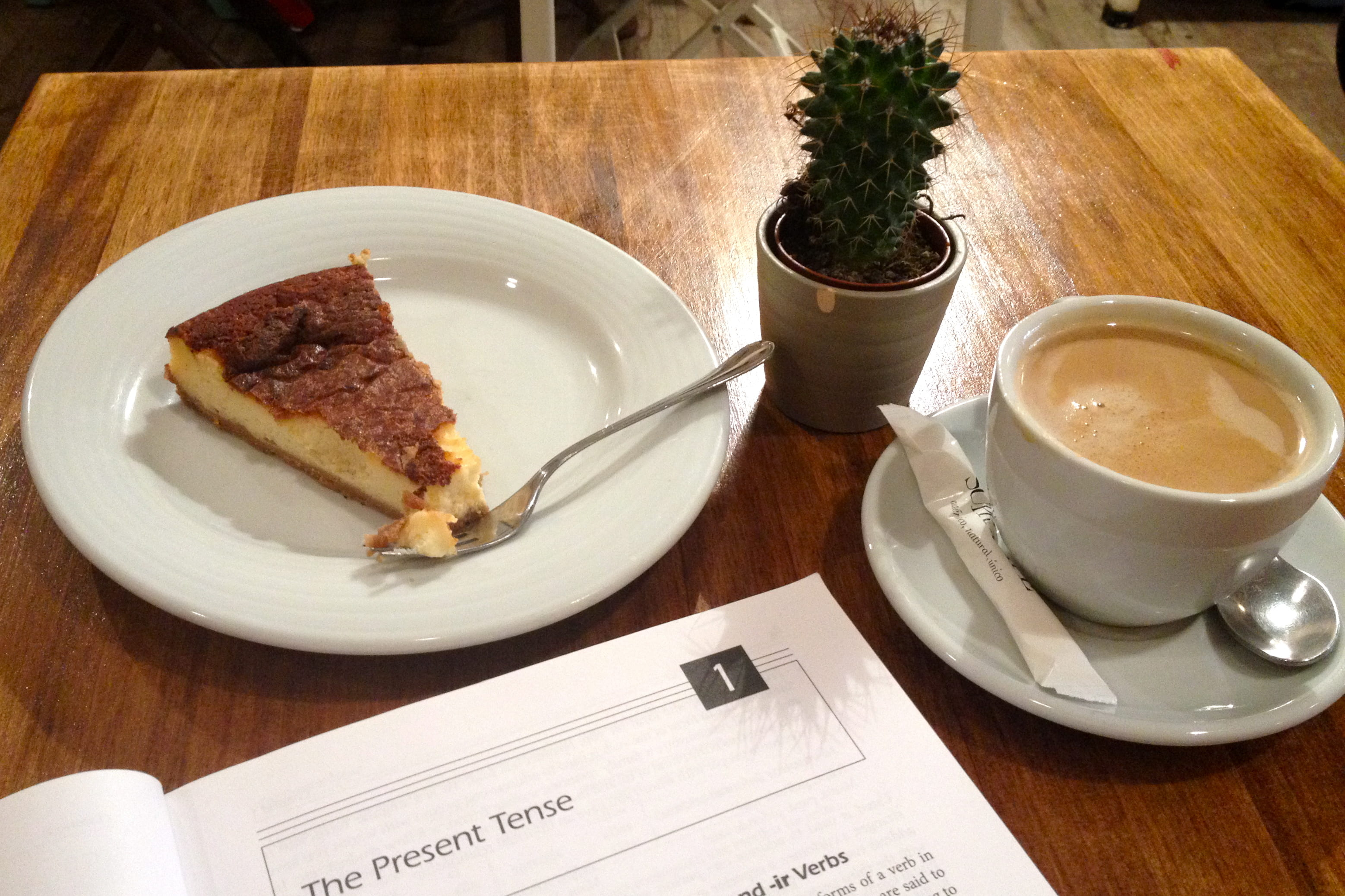 Spanish grammar book with dessert and coffee