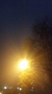 A street lamp shines on a foggy night at Oxford