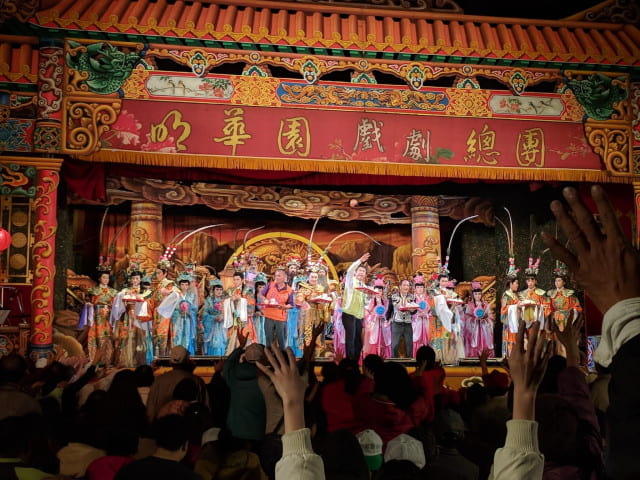 Front row view of performers on stage throwing buns