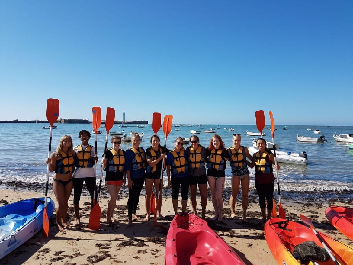 Students on beach with kayak paddles and kayaks