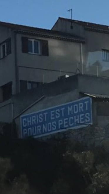 """Street sign in French saying, """"Christ est mort pour nos peches."""""""