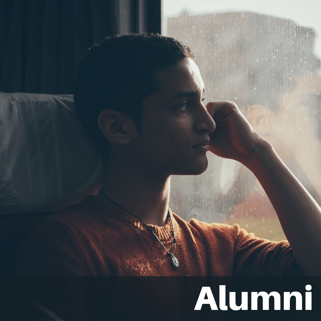 "Text on image ""Alumni"": Male student looking pensively out train window"