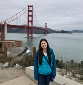 Julia in front of water and bridge