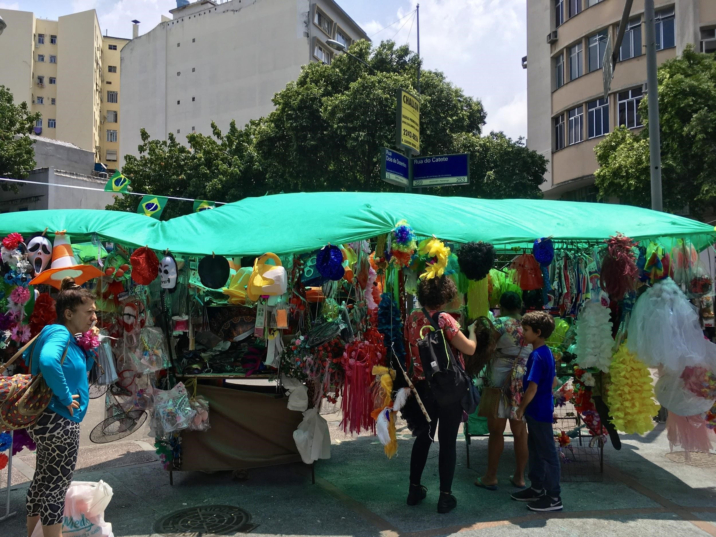 Street vendors selling costume items, such as colorful tutus, pirate hats, and bunny ears