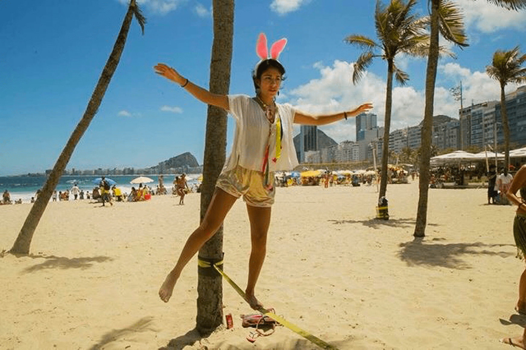 Esperanza walking on a low-to-the-ground tightrope on a beach in Rio de Janeiro