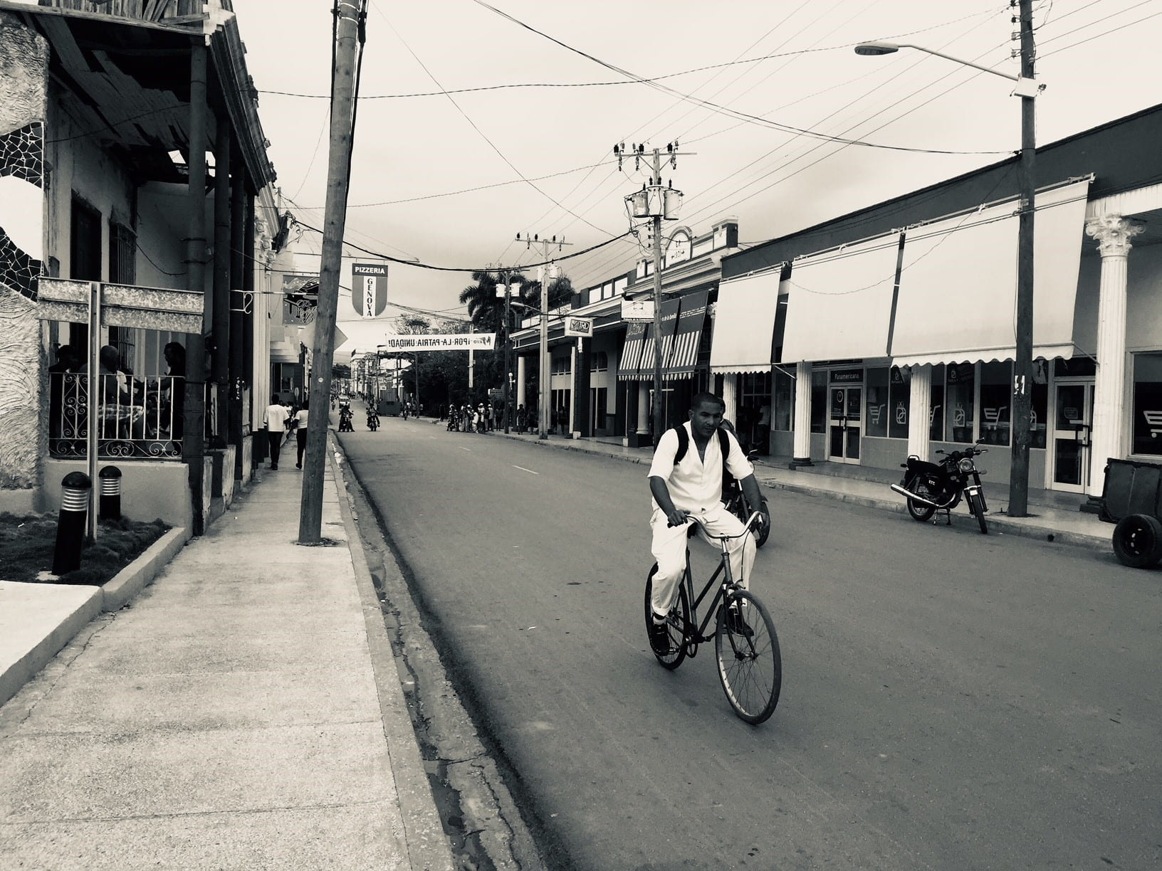 Black and white photo of person riding bicycle in middle of street in Havana, Cuba