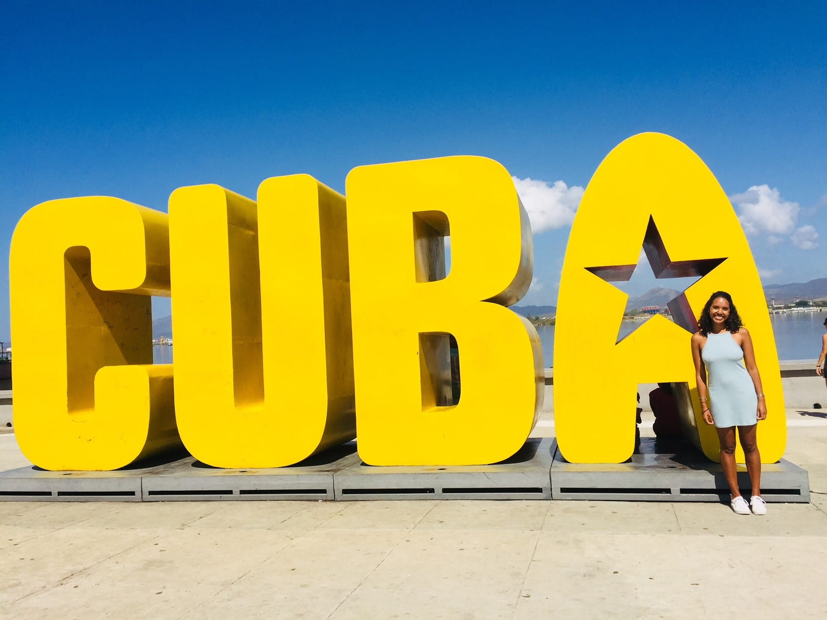 Bella standing in front of large yellow Cuba sign