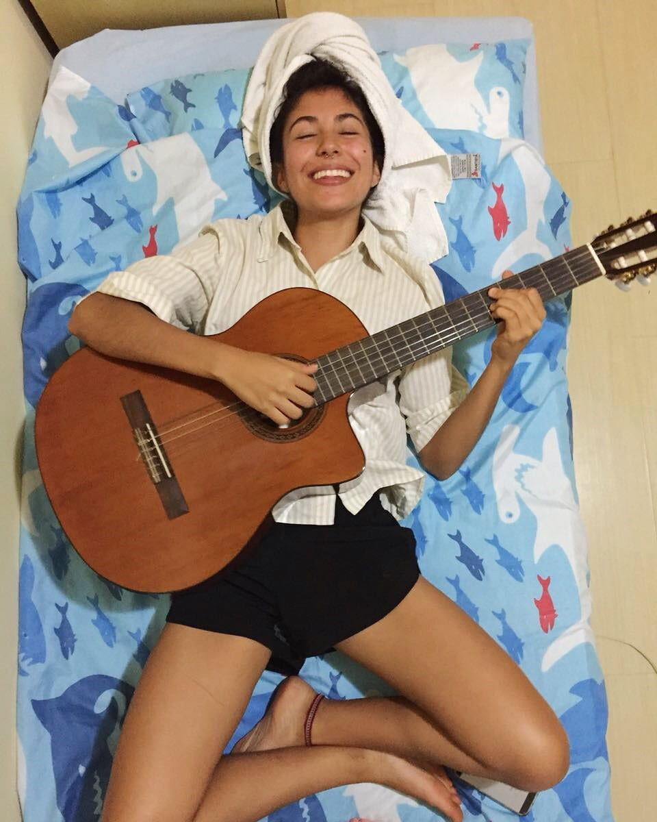 Esperanza lying on a bed, playing guitar