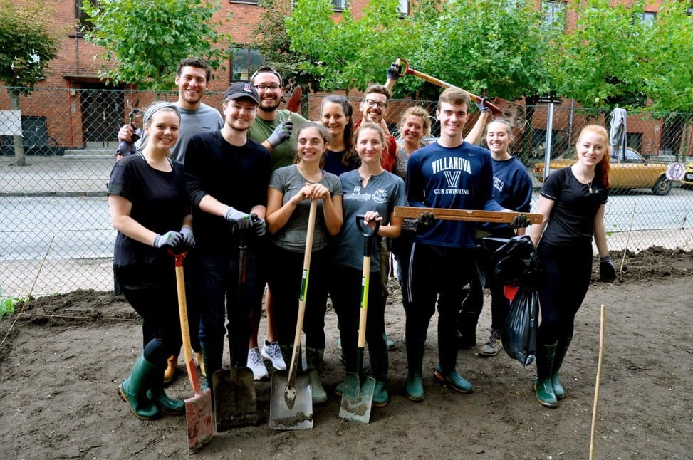 Talia with housemates volunteering and holding shovels