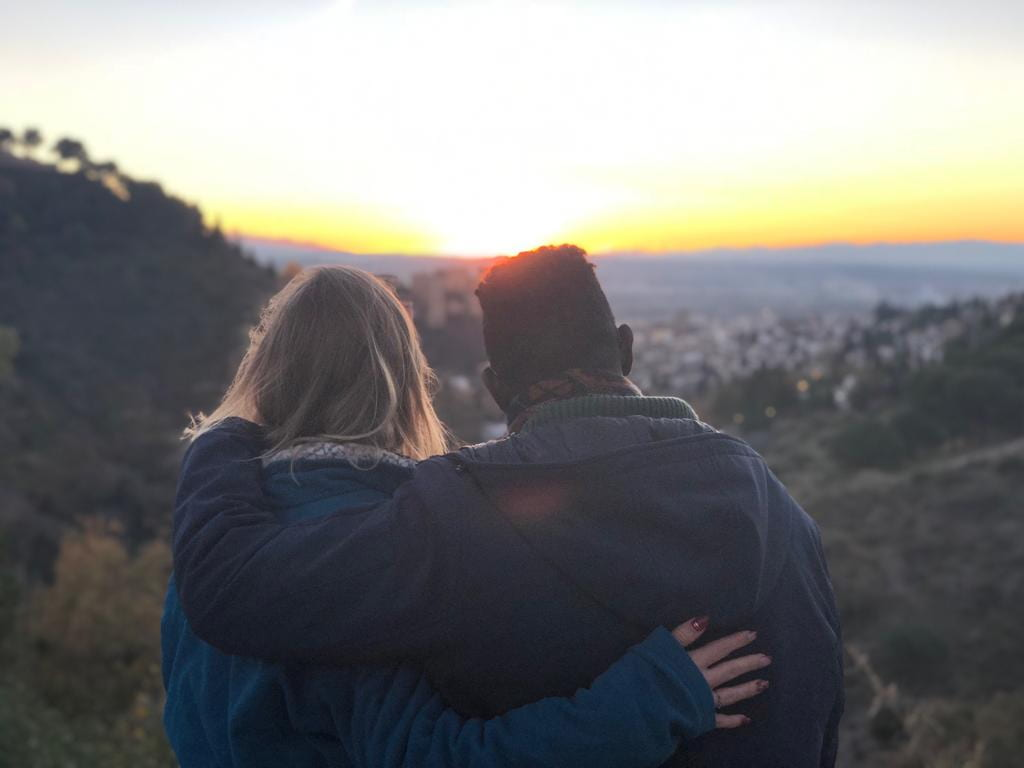 Anthony and friend sitting on hill facing sunset with arms around each other