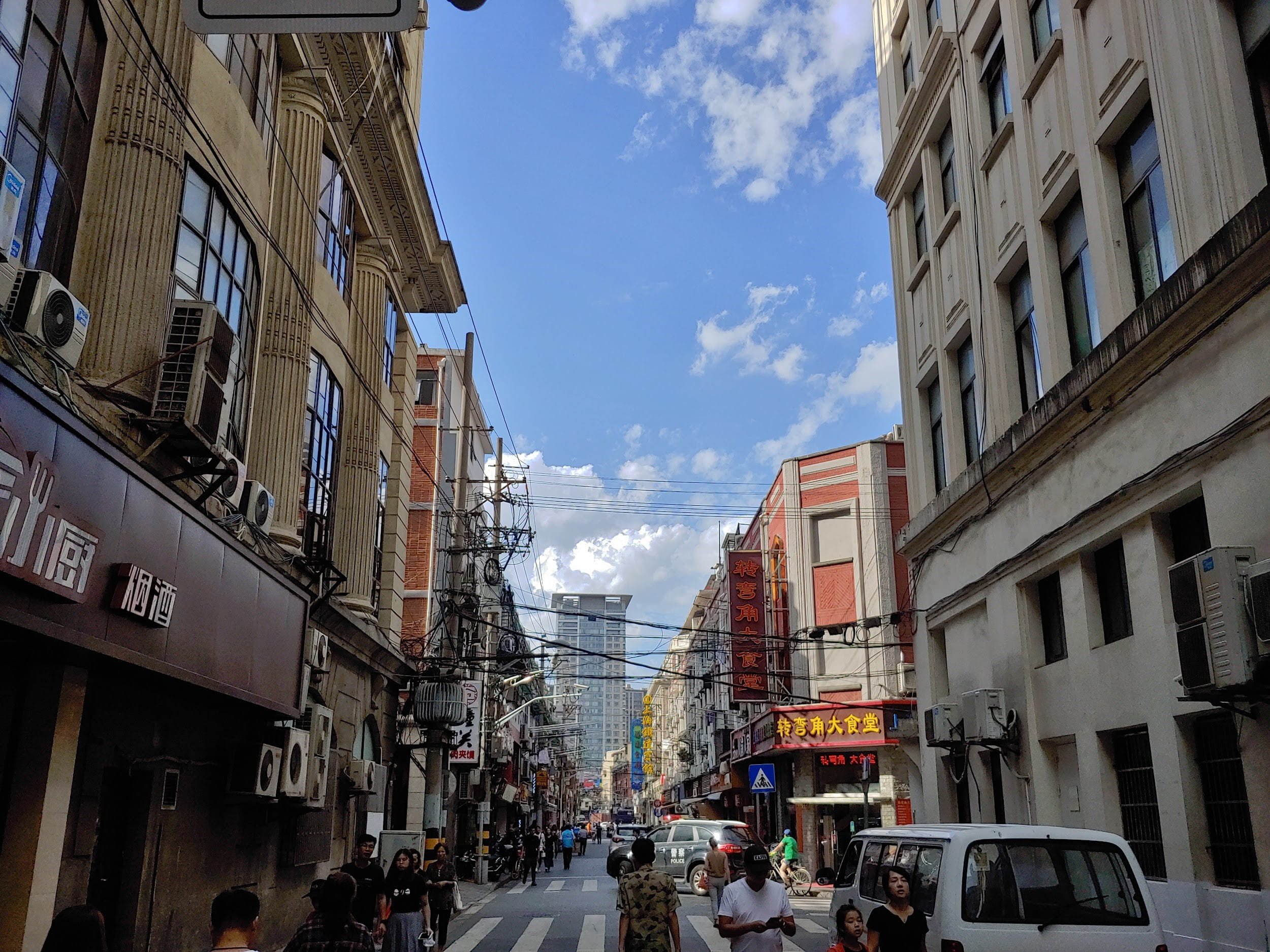 Looking down a street in Shanghai with buildings on both sides and blue sky and clouds in the background