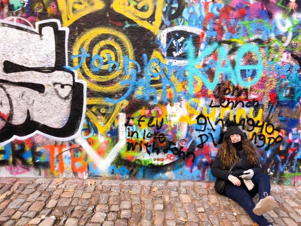 Talia sitting in front of John Lennon Wall in Prague