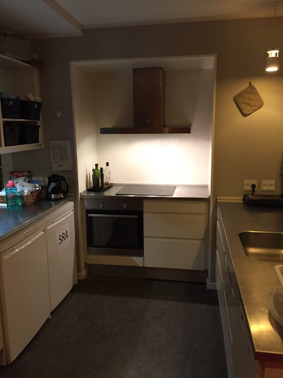 A dimly lit kitchen with white cupboards