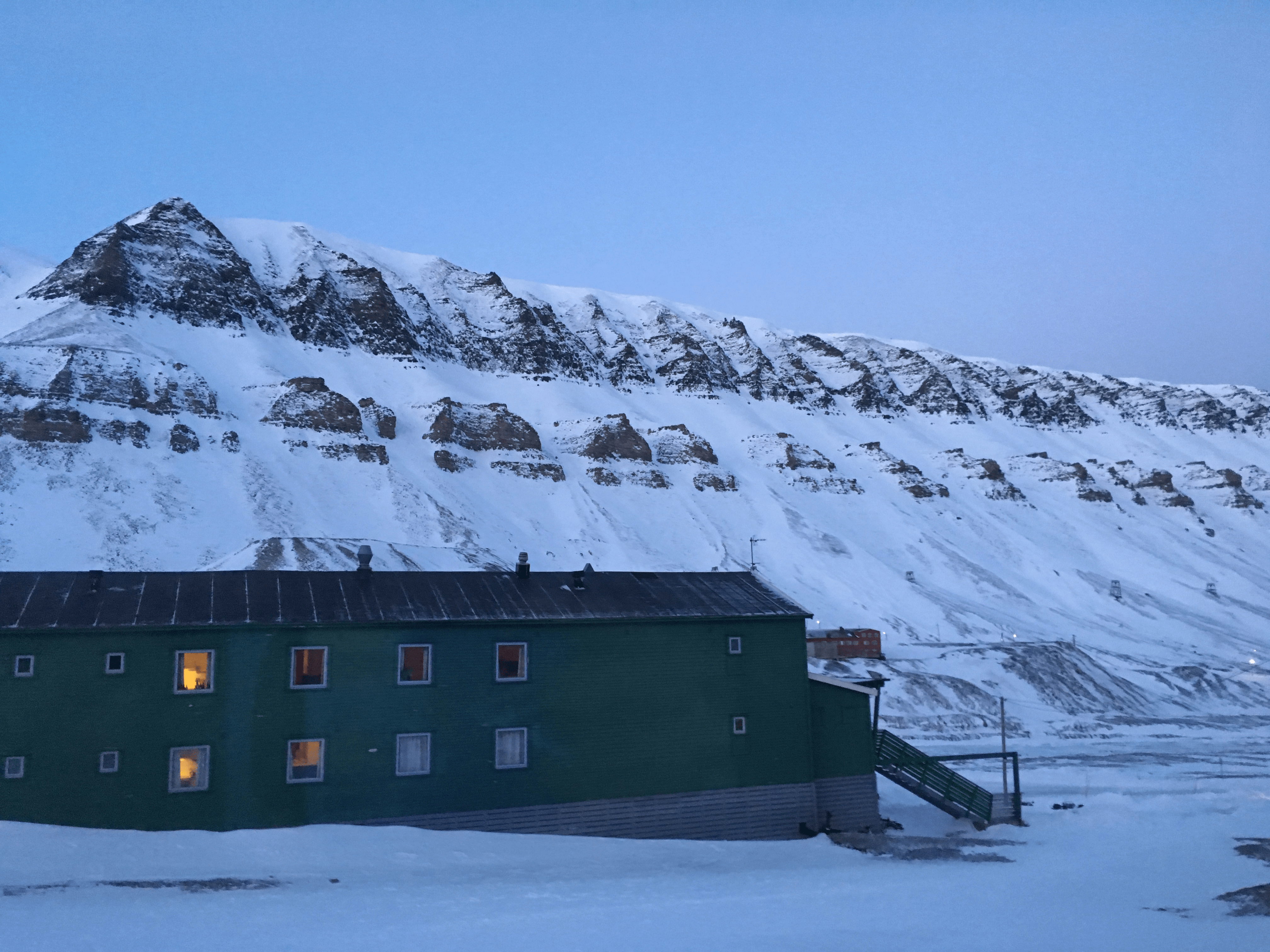 Green building with lights in windows, snowy mountain in background