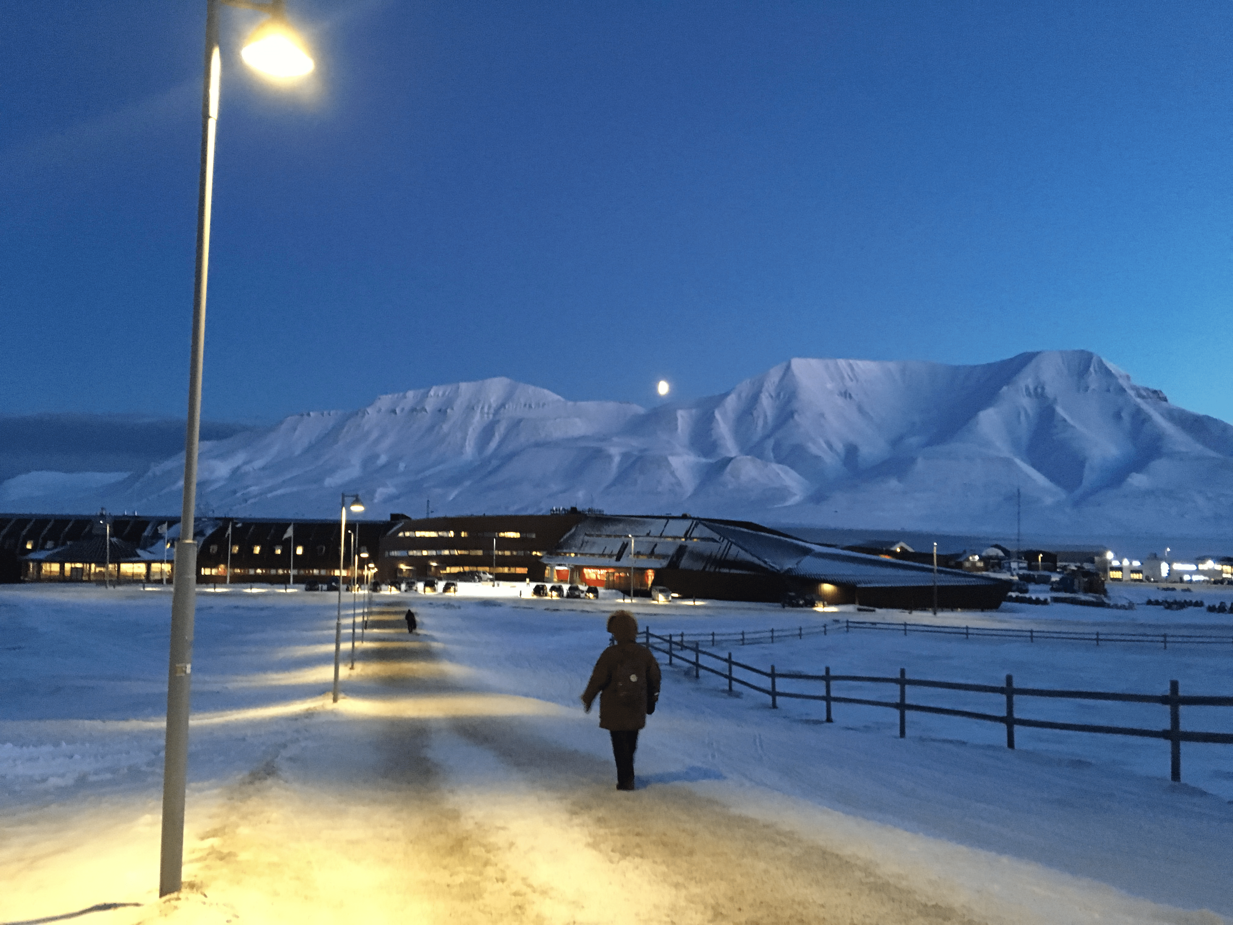 Student walking on dimly-lit path in snow with snowy mountains in background