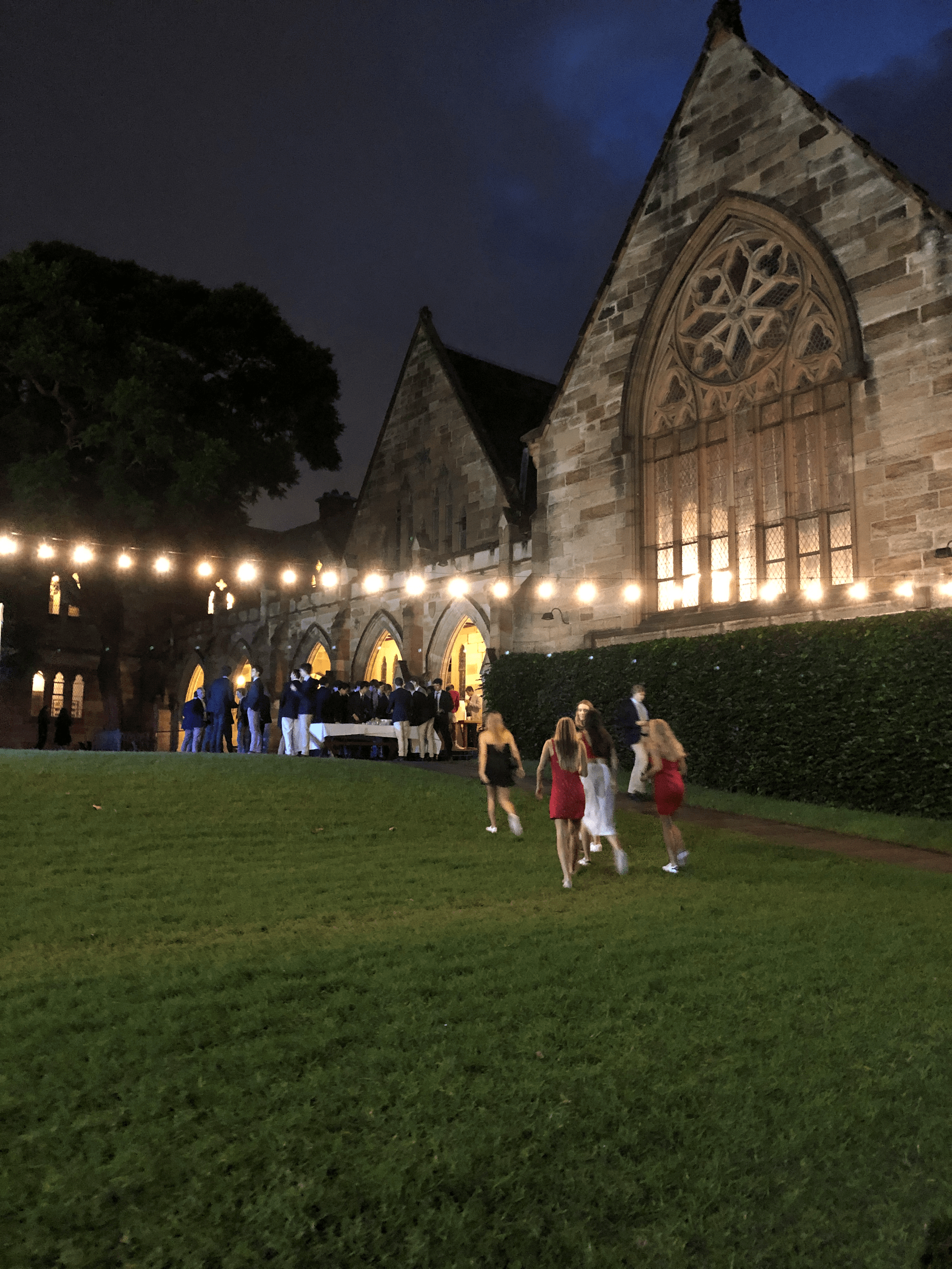 Old college building at night with string lights outside and students dressed up