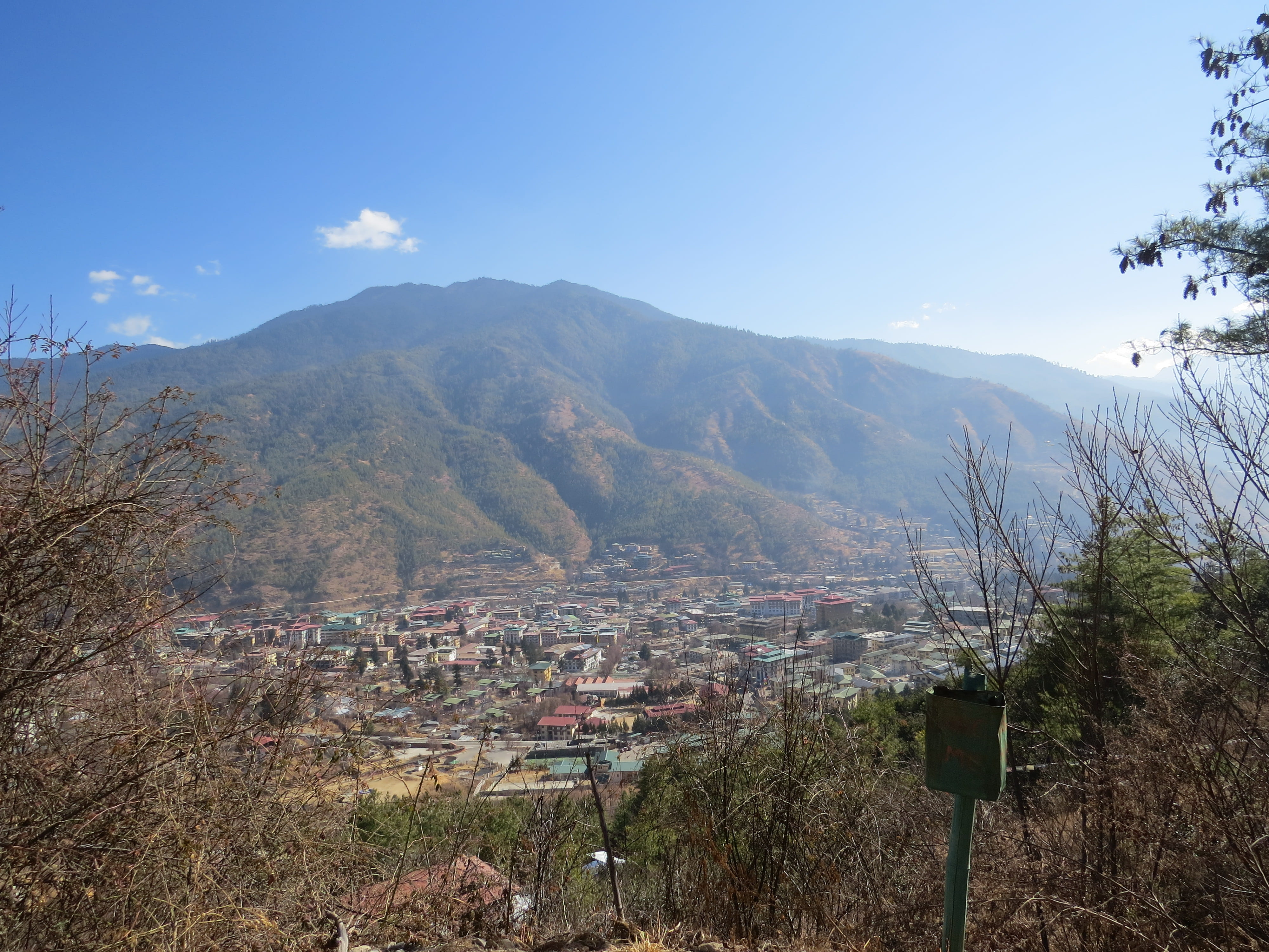View of Thimphu, Bhutan's capital, from above with mountains and blue sky in background