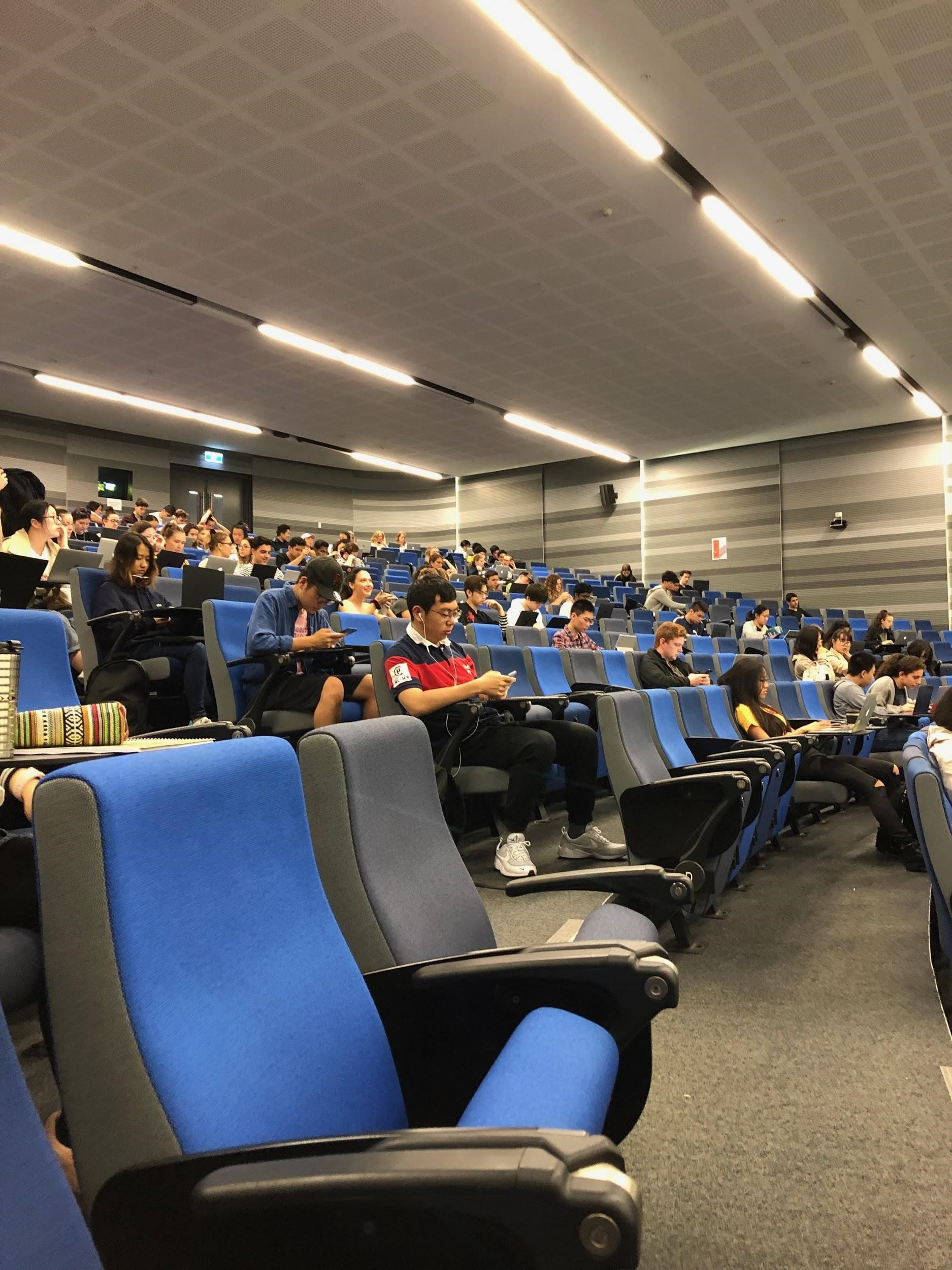 large lecture hall with blue seats and half full of students