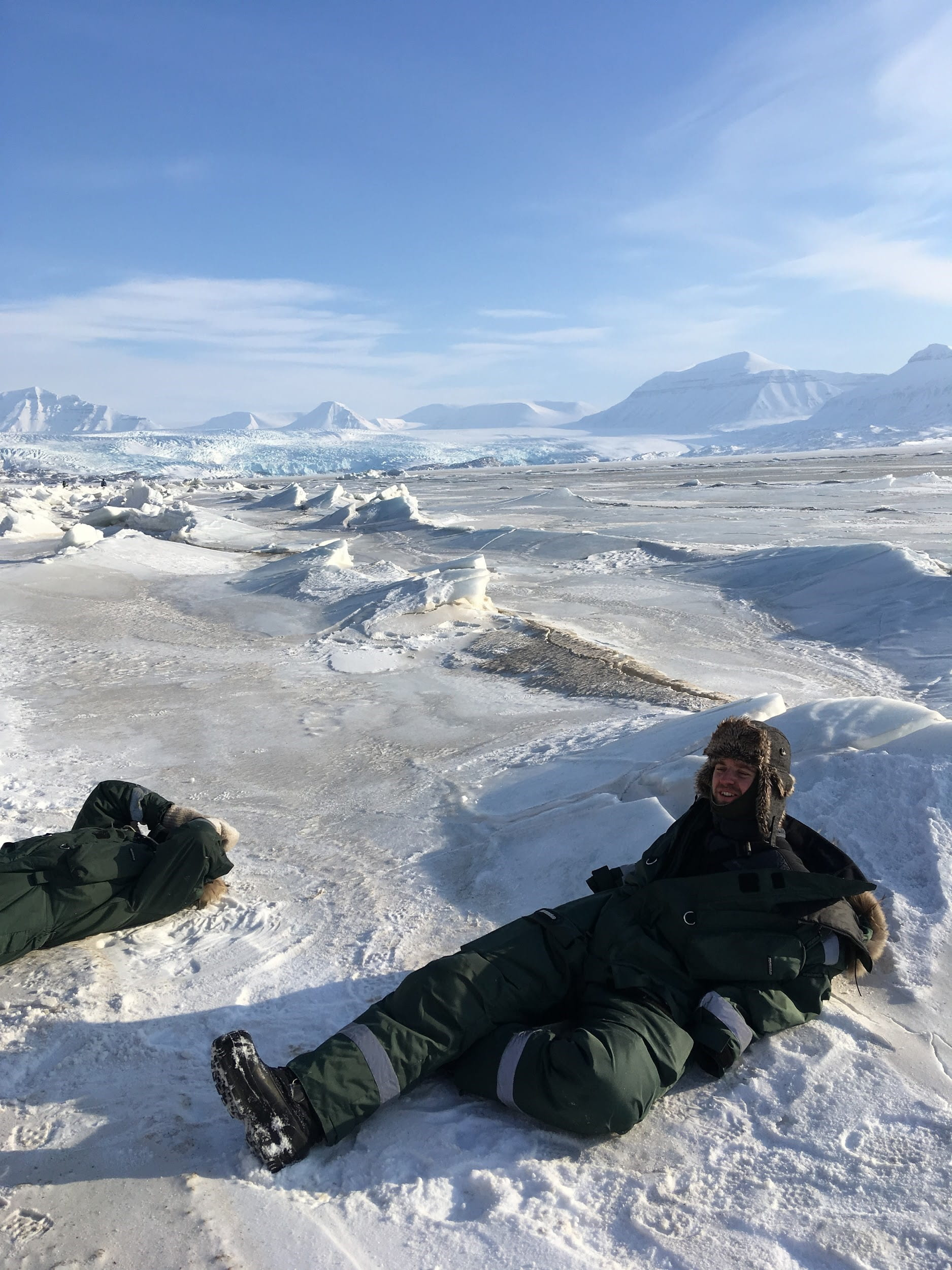 Two people bundled in winter clothing lounging on bed of snow and ice with blue sky in background