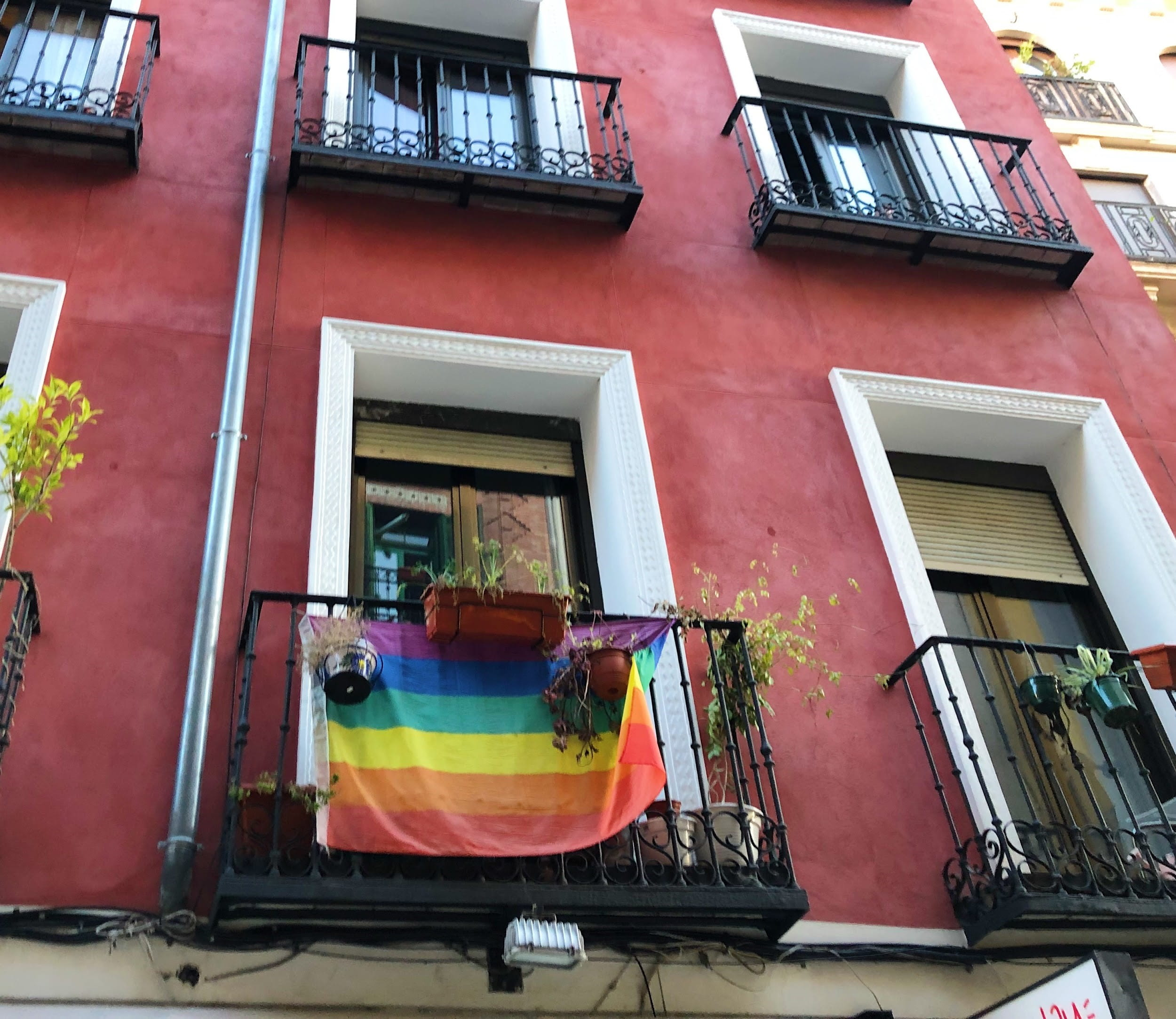 Red building with pride flag hanging from balcony