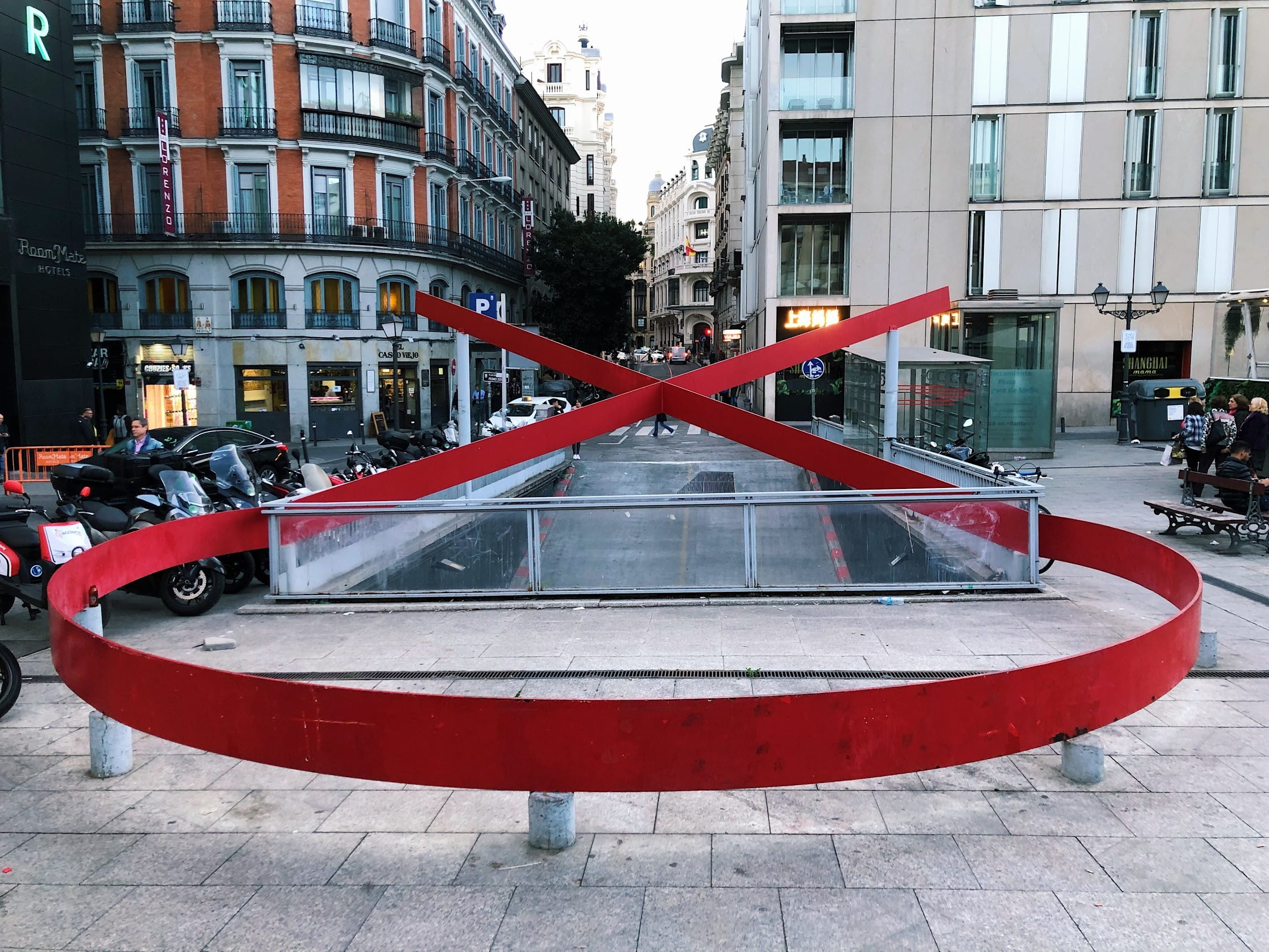 large red ribbon monument in front of tall buildings