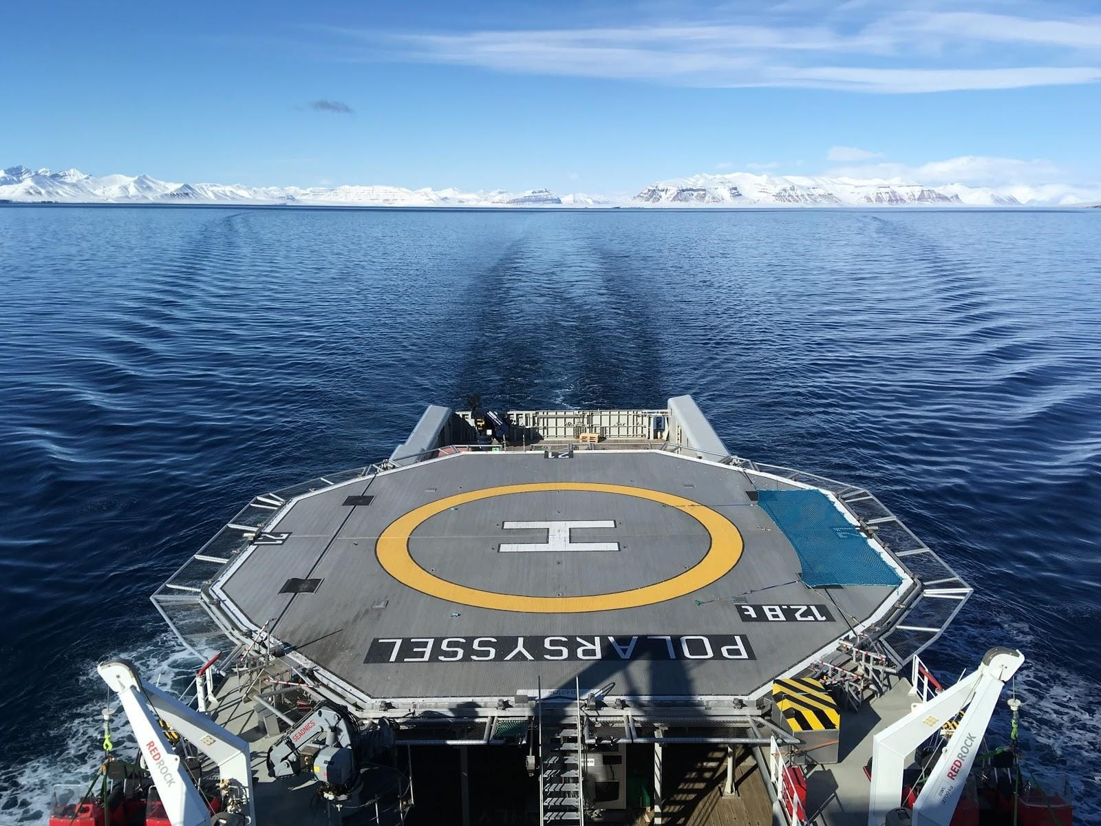 Large flat, government boat with letter H in yellow circle in Arctic waters