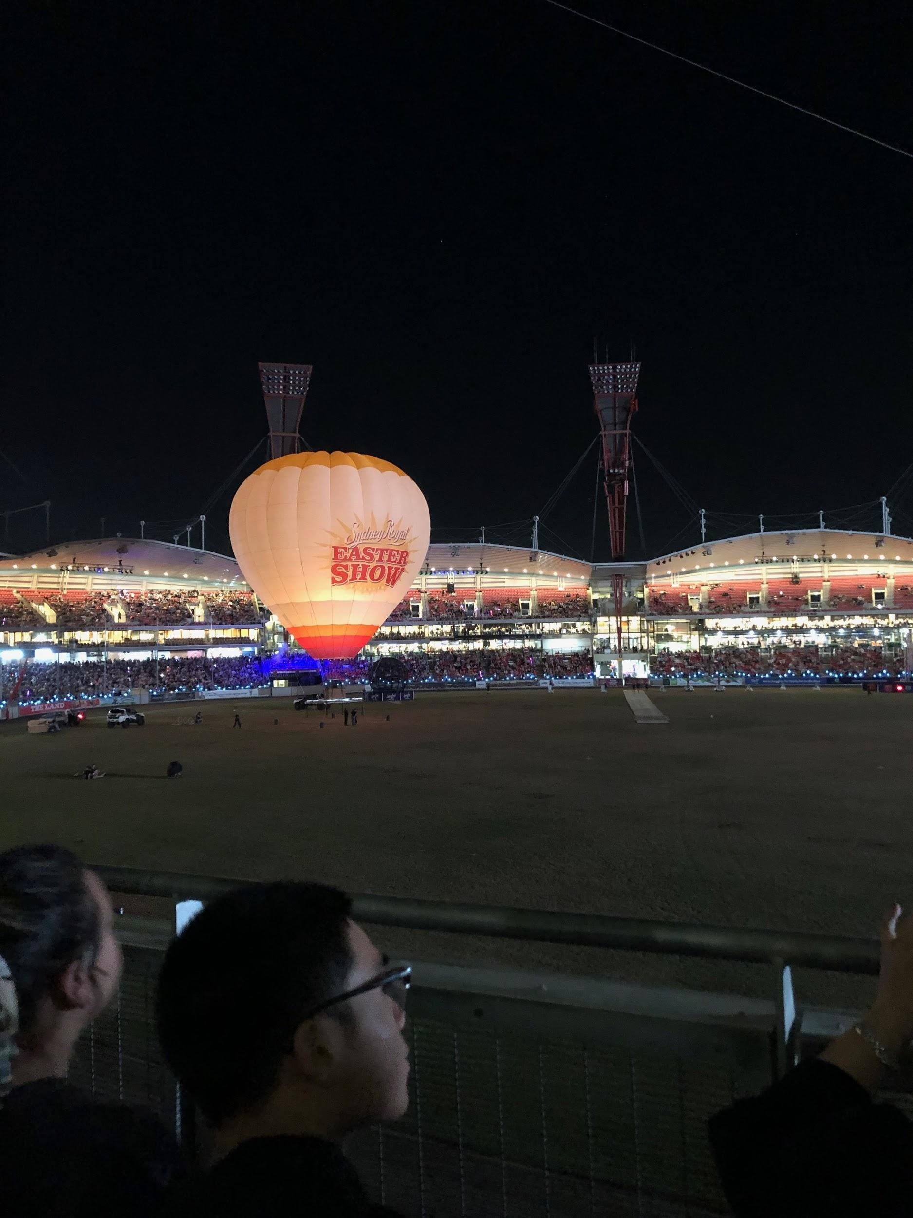 Hot air balloon on grass in stadium at night with bleachers and lights in background
