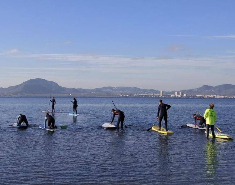 Stuart and seven others in water on paddle boards, mountains in the background.
