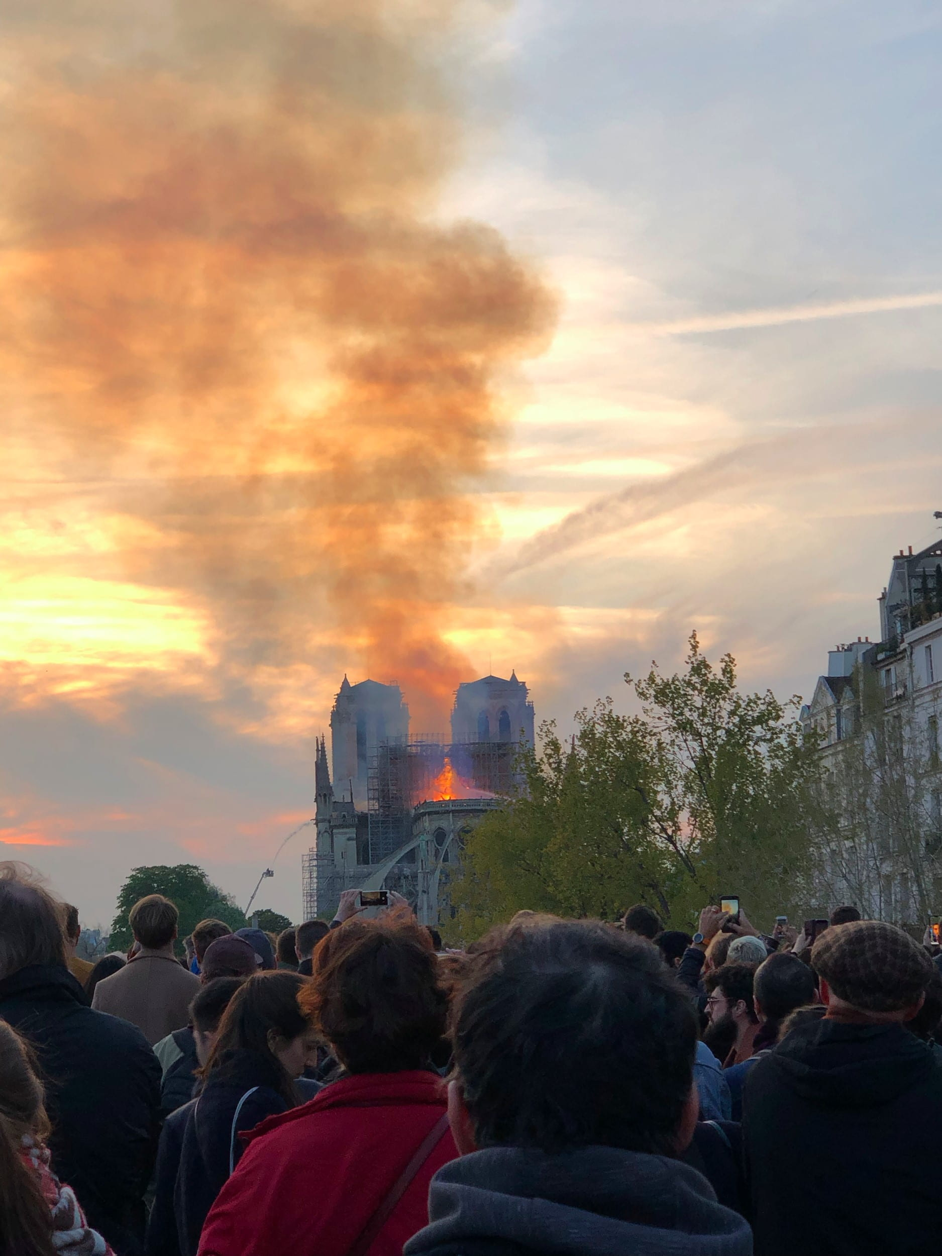 Lots of people watching the Notre Dame in Paris burn, flames and lots of smoke in the background