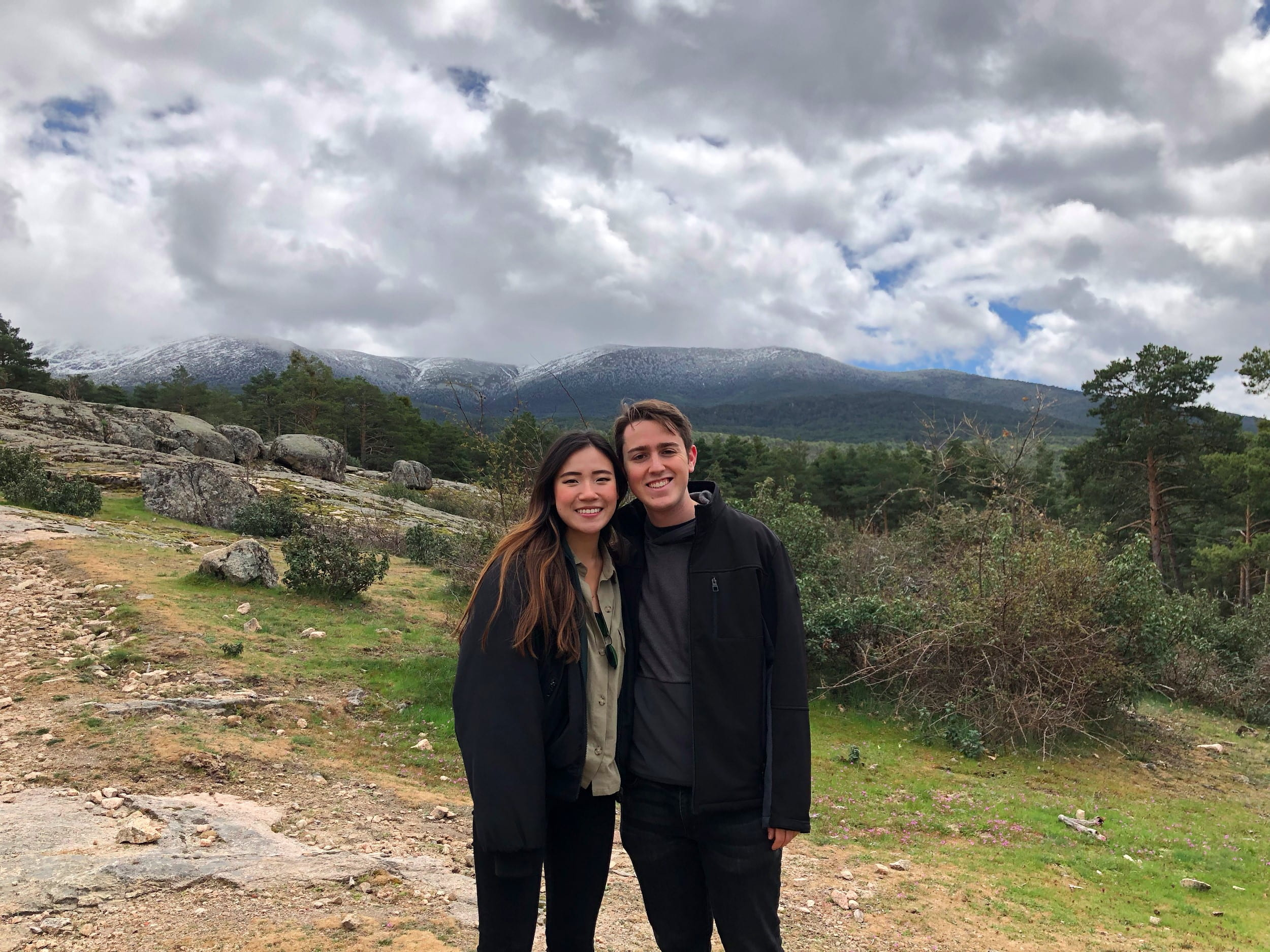 Stuart standing next to friend posing for photo in front of mountainous landscape and cloudy sky