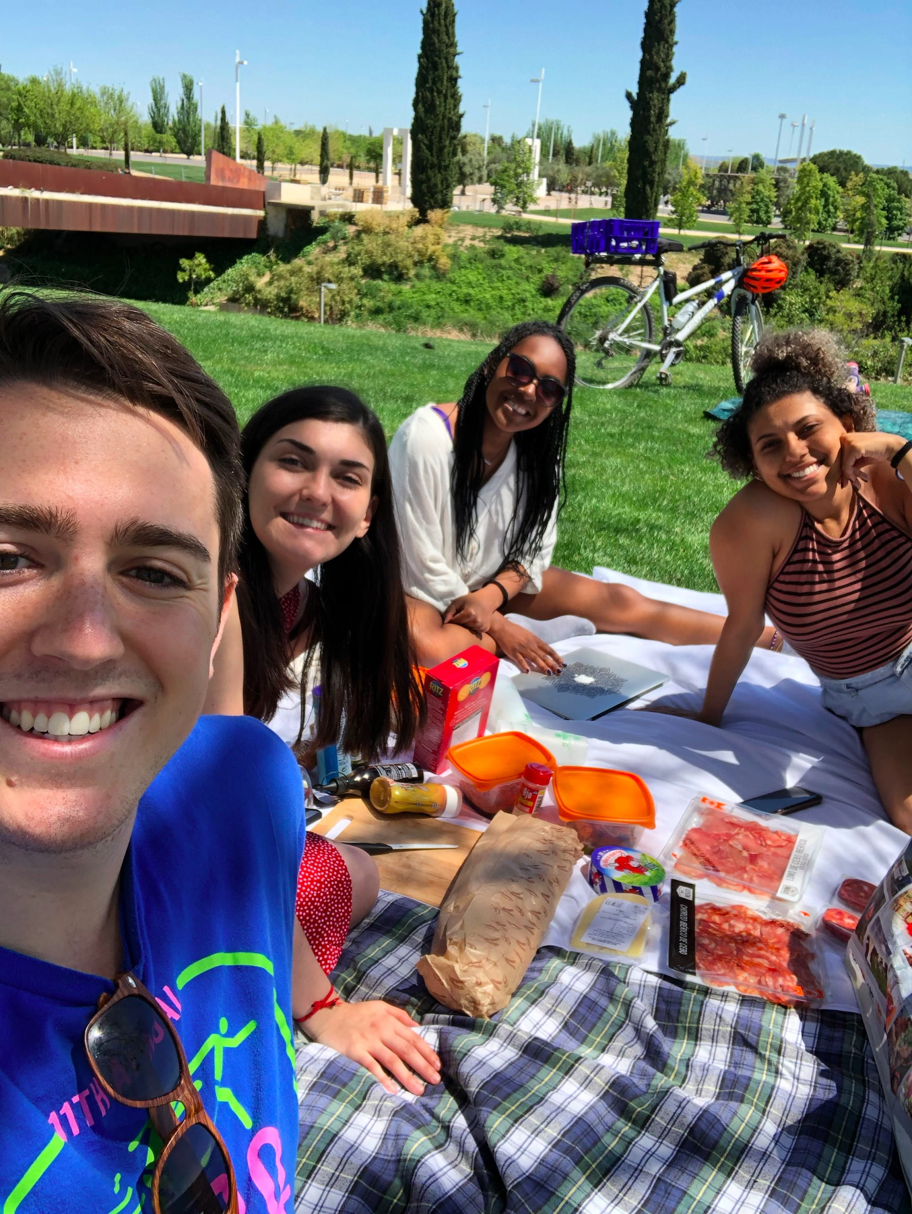 Four students sitting on white blanket with food for picnic and green grass and bicycle in background