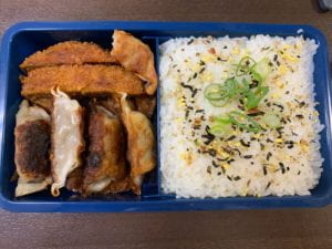 A bento box with gyoza and white rice