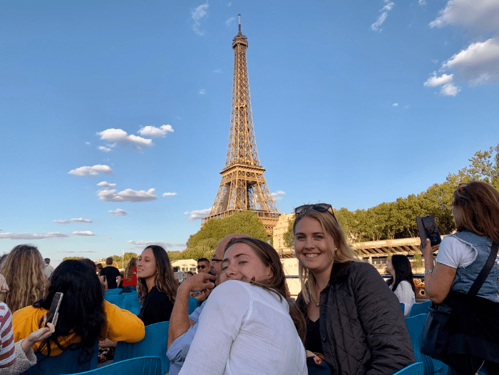 Two girls on a boat in front of Eiffel tower on Seine River