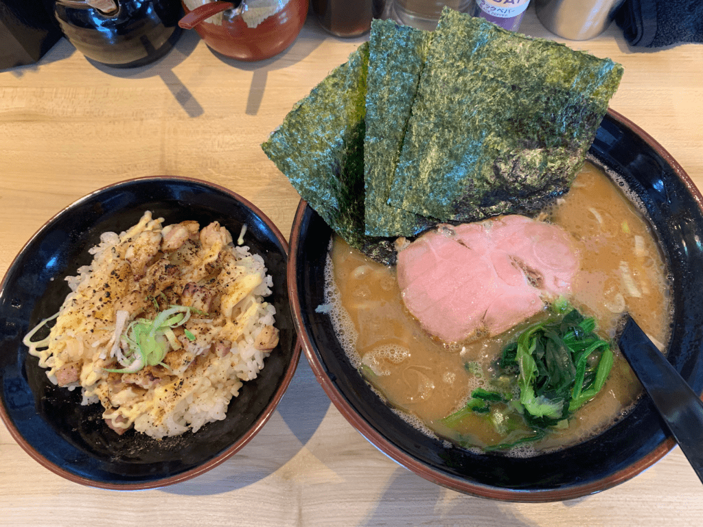 A large bowl of ramen and smaller bowl of noodles