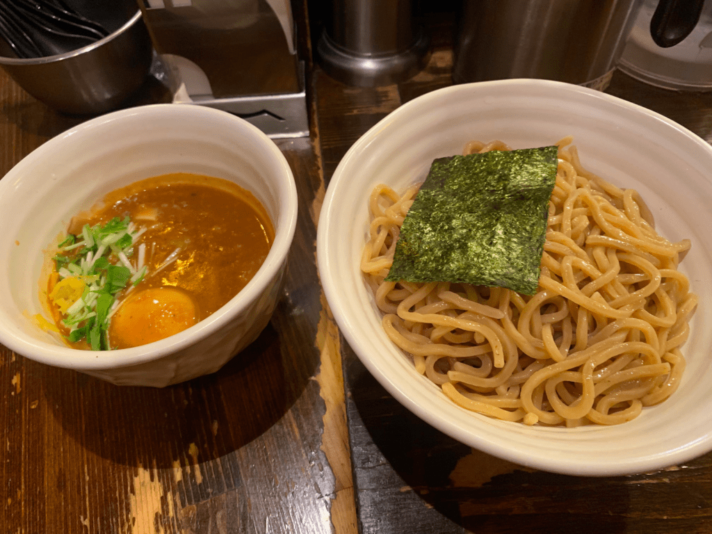 A serving of Tsukemen ramen- a bowl of noodles with a bowl of soup dipping base next to it