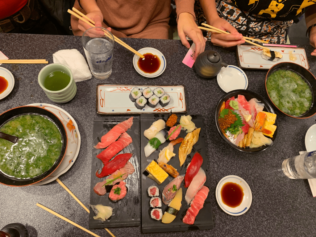 Multiple plates and bowls of sushi, sashimi, and miso soup.