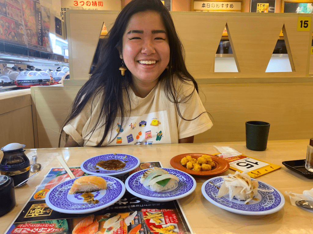 Cy smiles with plates of sushi on a table in front of her