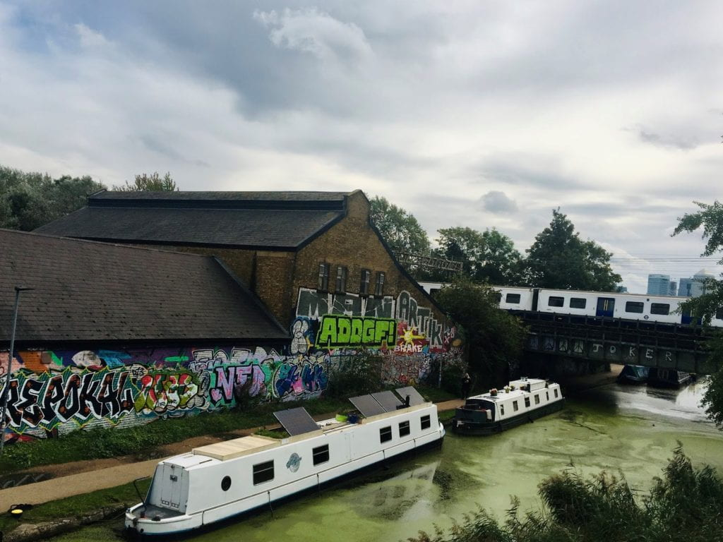Two boats sit in a polluted river in front of an old building covered in graffiti