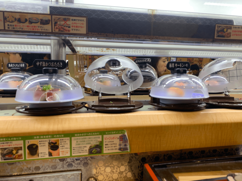 A conveyer belt with plates of various types of sushi