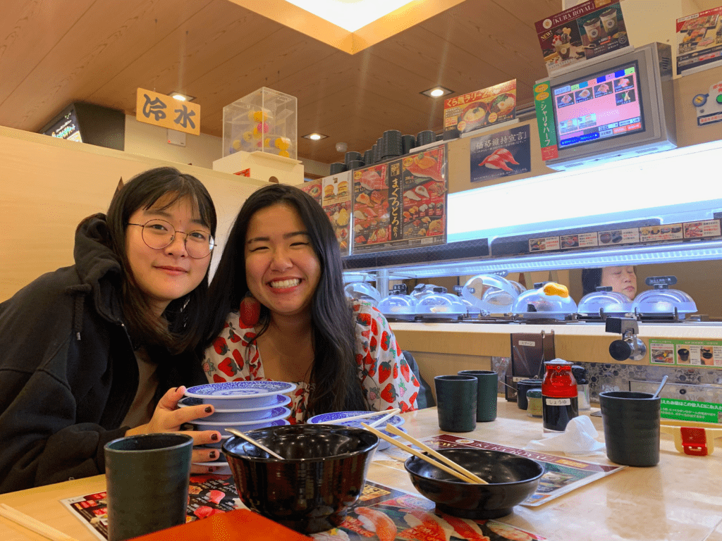 Cy and a friend smile at a table with multiple empty plates and bowls on it