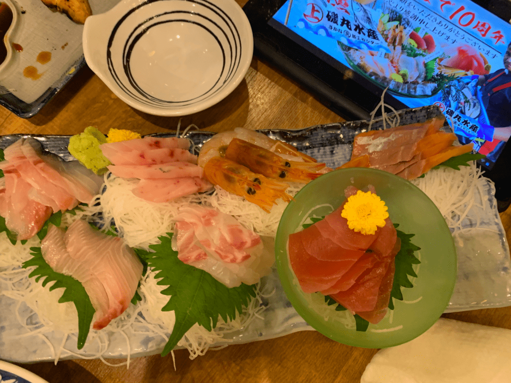 A serving plate with sashimi and garnishes