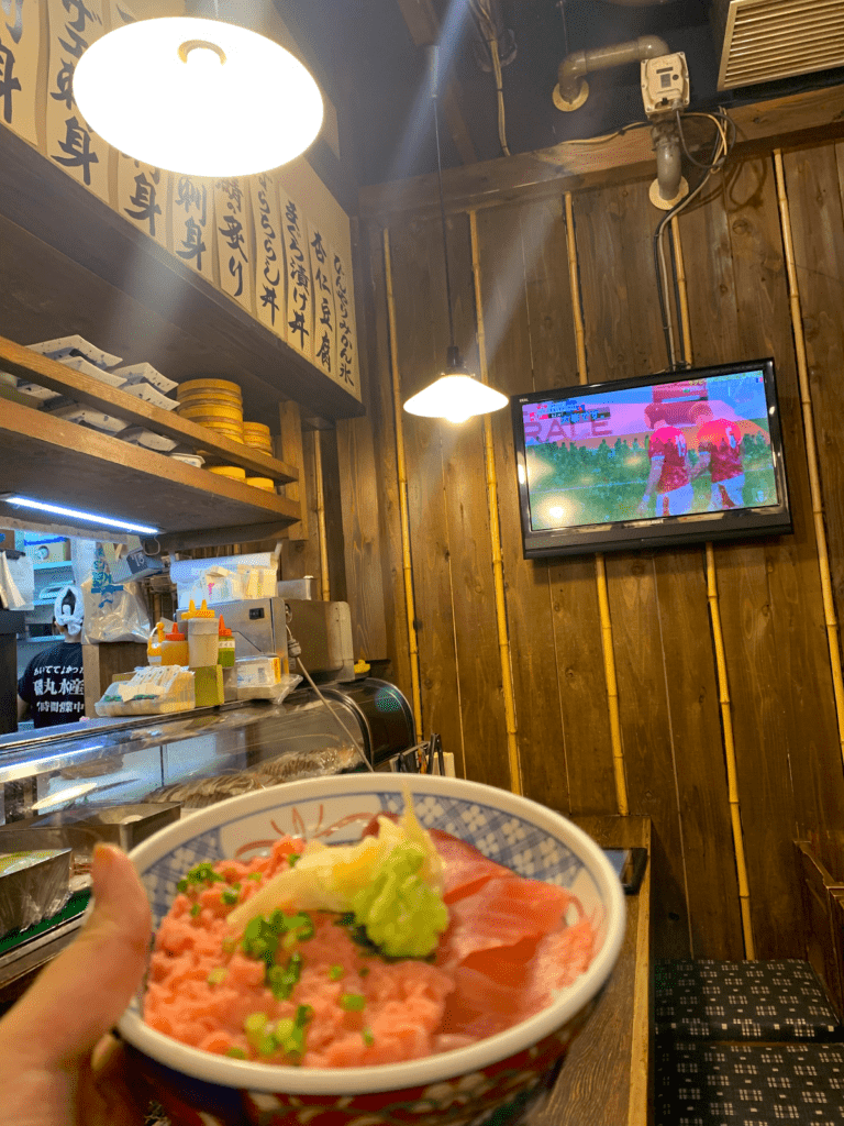 Cy holds up a bowl of fresh tuna in front a TV playing a rugby match